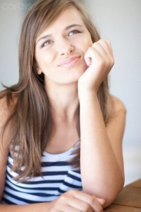 Teenage girl thinking with chin in hand