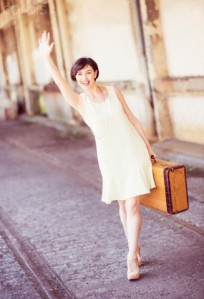 Woman in dress holding suitcase at train station, waving hand